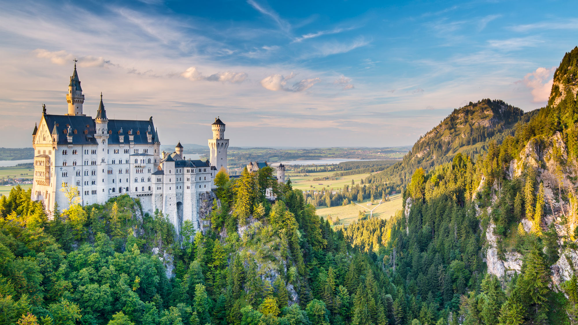 Exterior of the Fussen Neuschwanstein Castle in Germany surrounded by mountains and forests