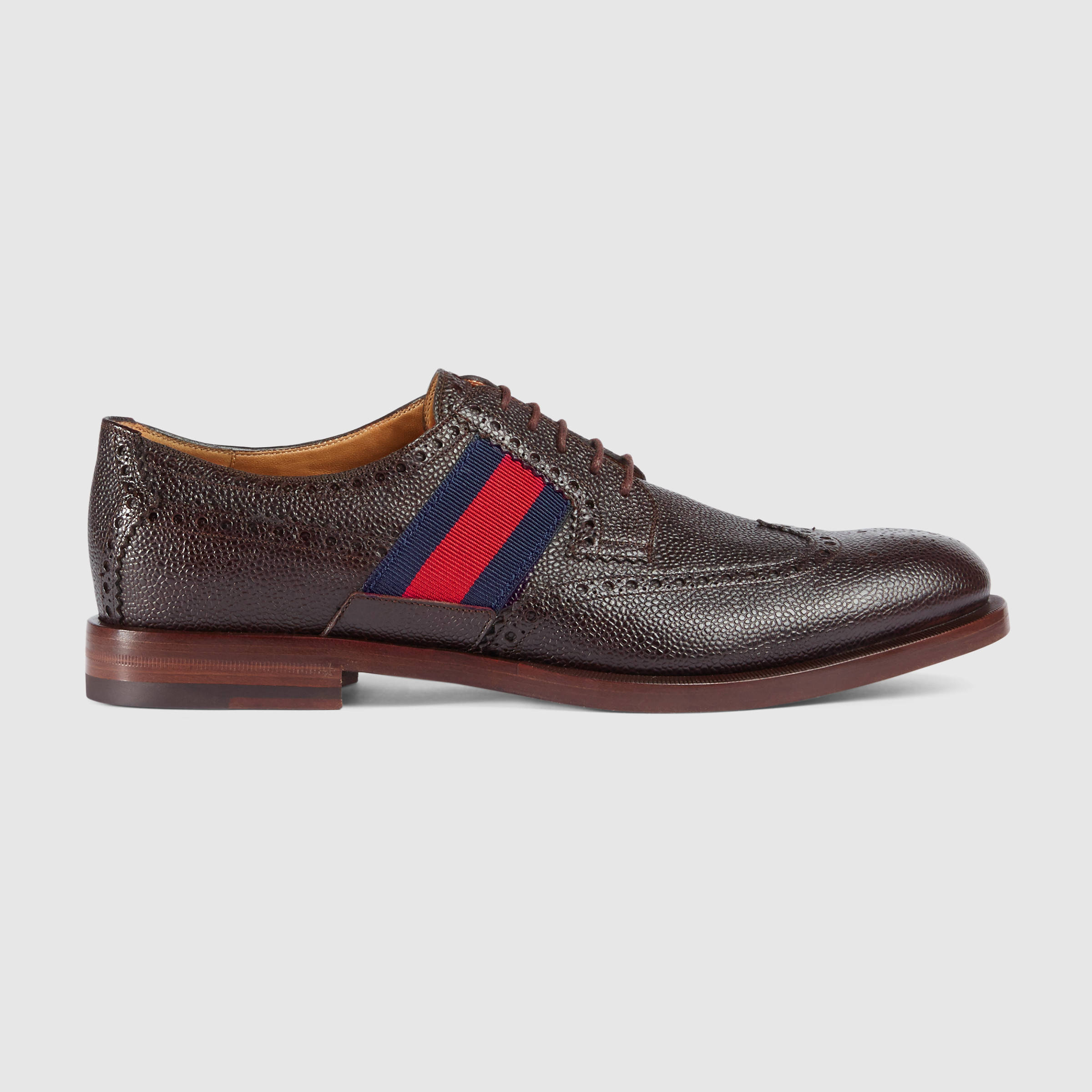 Gucci's lace-up dress shoe in textured leather with perforated details and striped accents