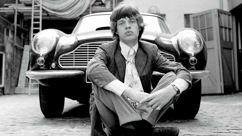 Mick Jagger in 1966 with an Aston Martin DB6