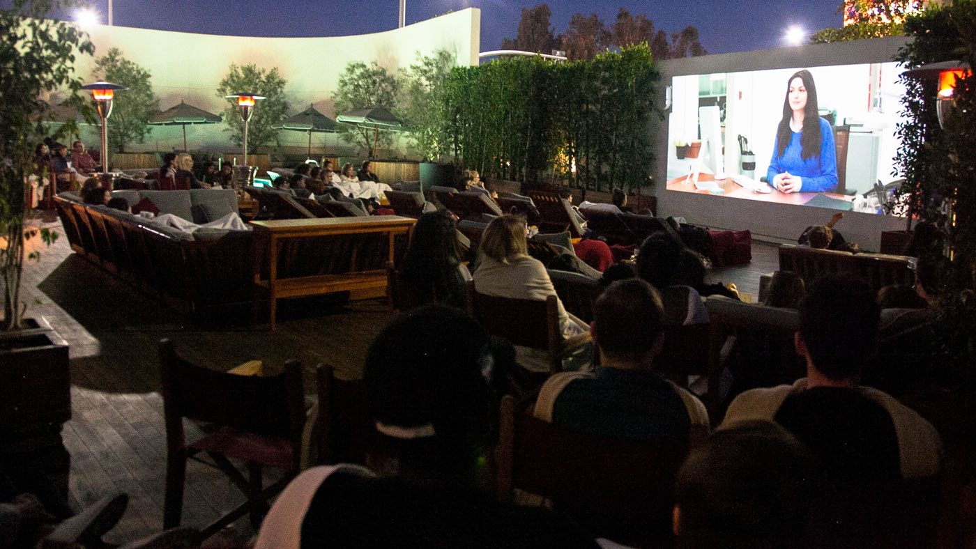 An outdoor movie is played, while people lounge in the garden