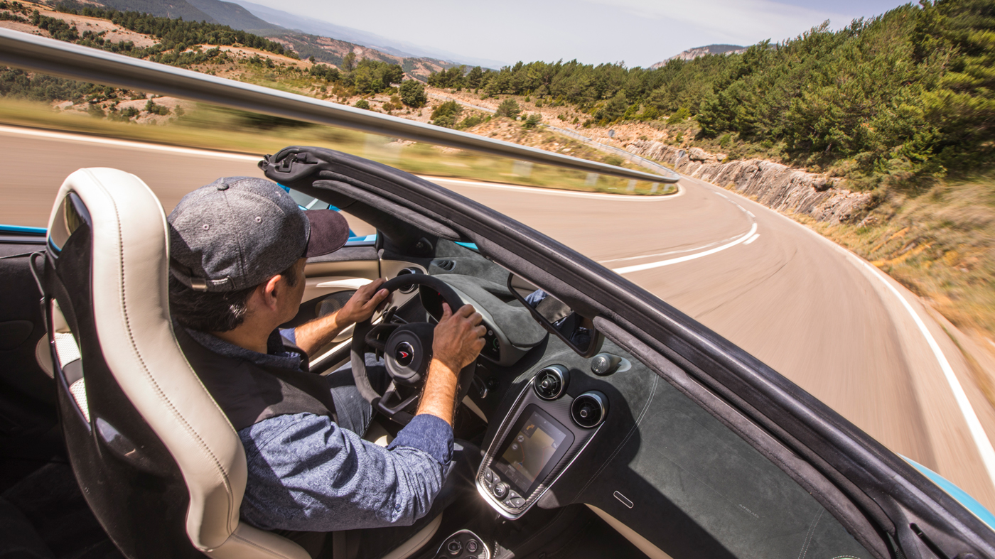 An image of a man driving the McLaren 570S Spider in the mountains outside of Barcelona.
