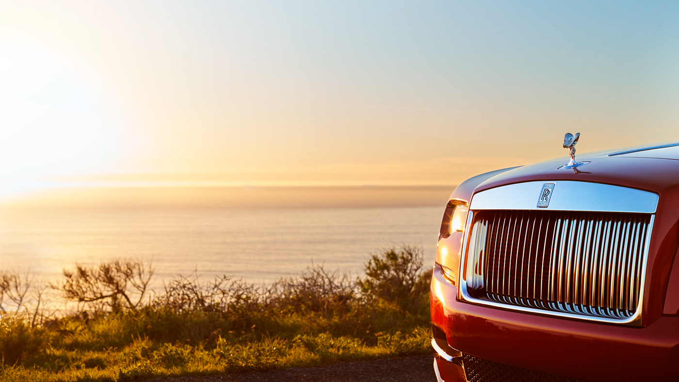 An image of the front of a Rolls-Royce car in front of a coastal cliff.