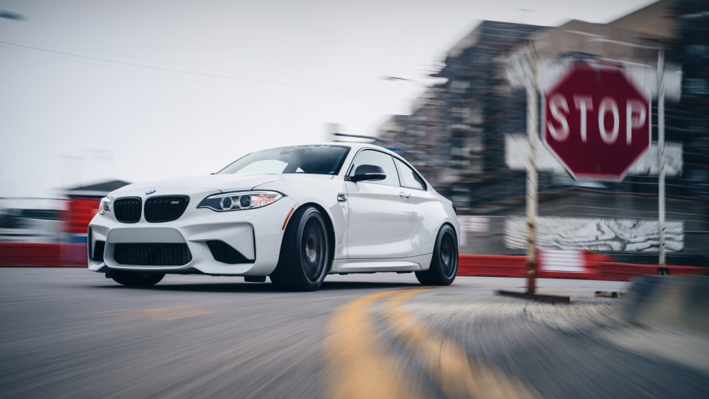 A photo of the Dinan BMW S2 M2 being driven in a city.