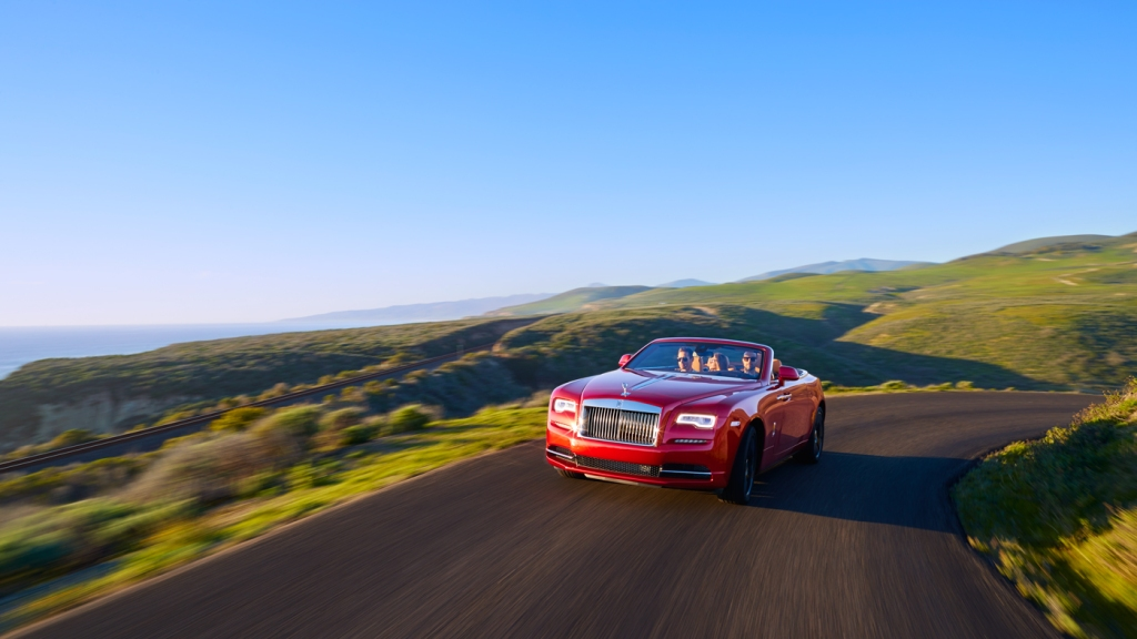 An image of the Rolls-Royce Dawn on a coastal country road.