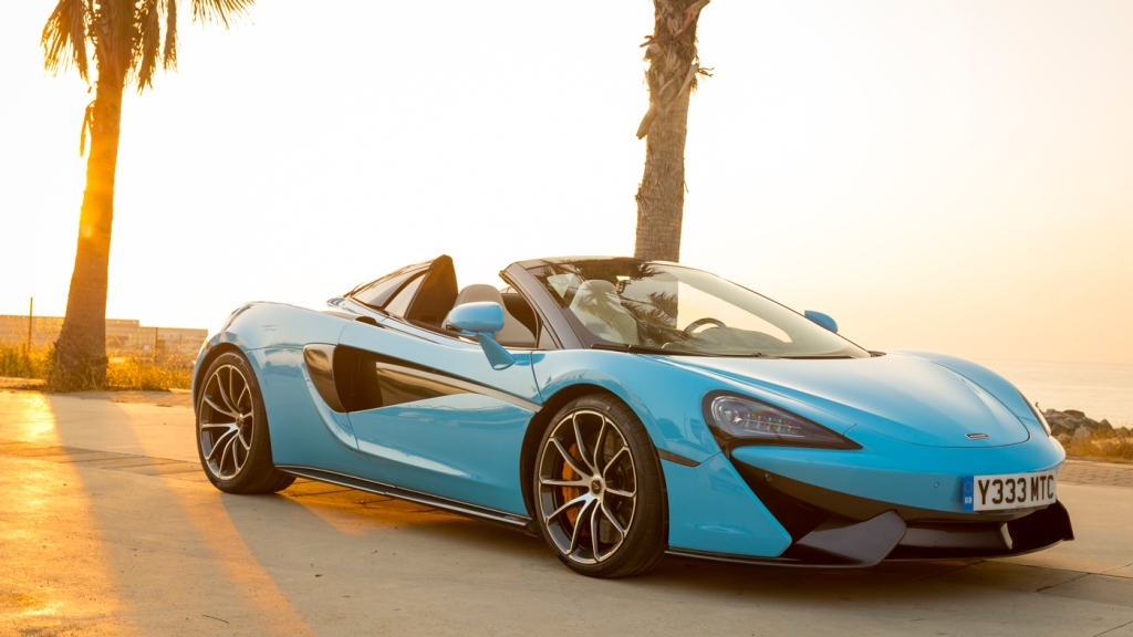 An image of a McLaren 570S Spider parked in front of a Barcelona beach.