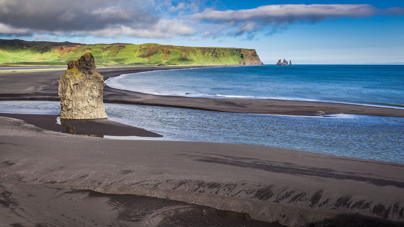 black sand beach with a giant rock and a cliff in the horizon