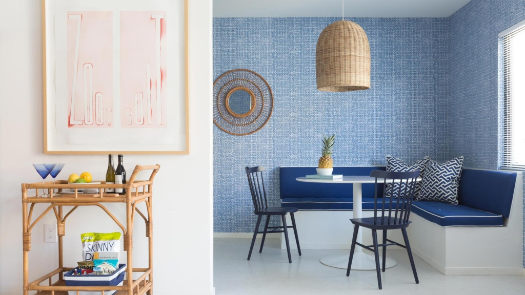 Room with blue wallpaper, table, and chairs.