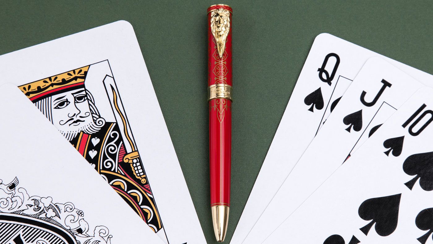Red and gold pen with playing cards