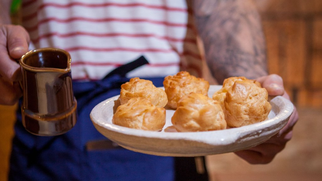 Profiteroles on a white plate with a pouring dish and a man's tattooed arm