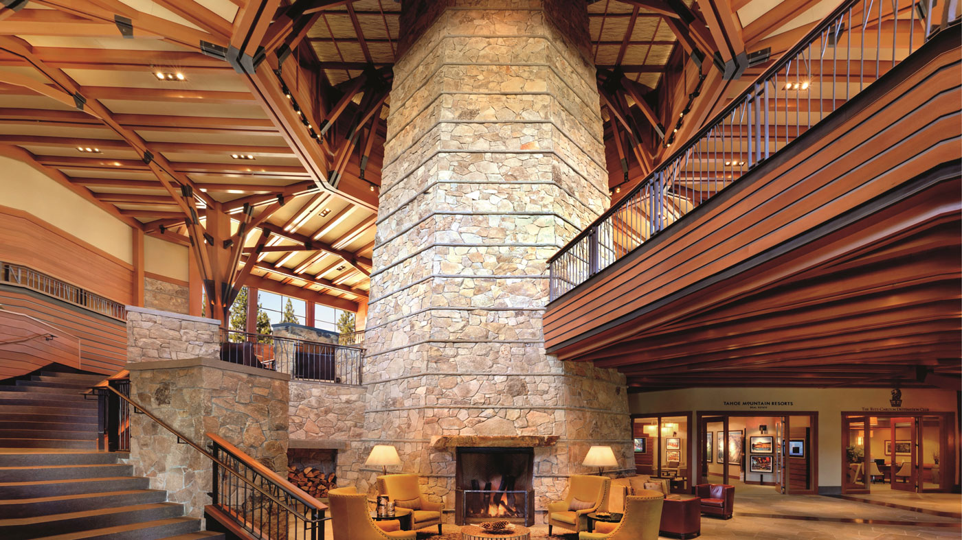 A wooden spiral staircase surrounds a pillar of stone and a fireplace