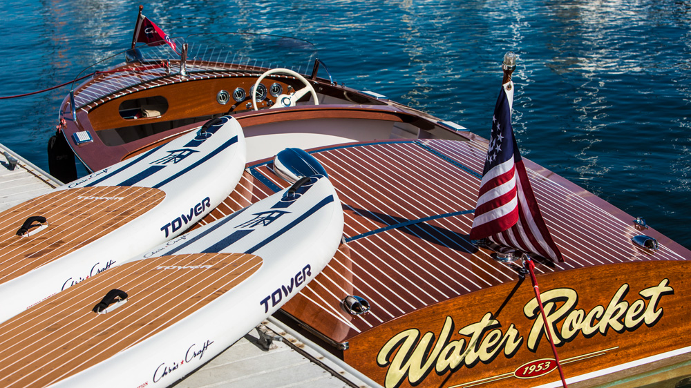 tower and chris craft paddle board next to wooden chris craft boat