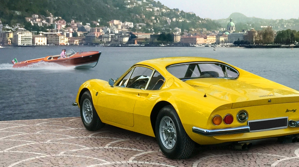 A Ferrari Dino 246 GT parked along the edge of Lake Como with a Riva speedboat in the background.