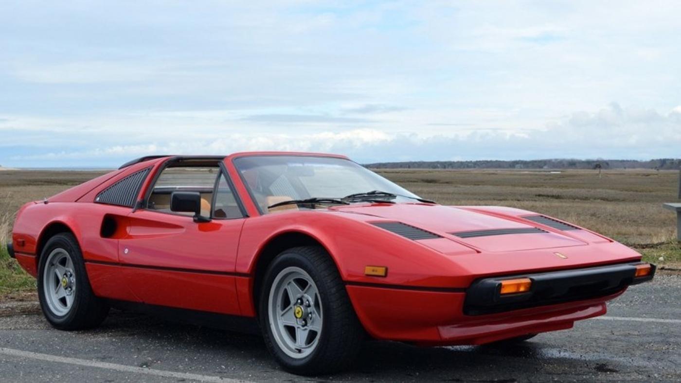 A 1984 Ferrari 308 in a rural parking lot.
