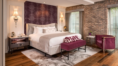 hotel room with wood floors brick walls large headboard