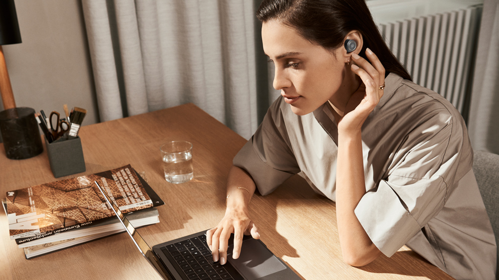 Beoplay E8 earbuds in woman working on laptop's ear