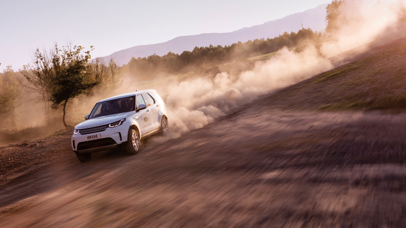 A Land Rover Discovery kicks up dust on a dirt road in Namibia.