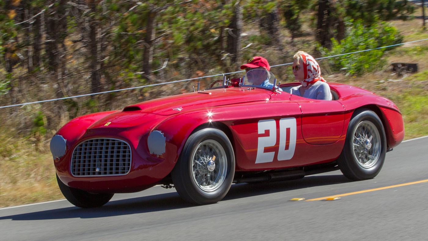 A couple drives a classic Ferrari as part of the festivities related to the Pebble Beach Concours d'Elegance.