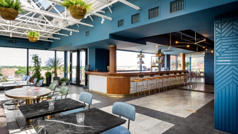 restaurant with blue walls, hanging plants, and bar