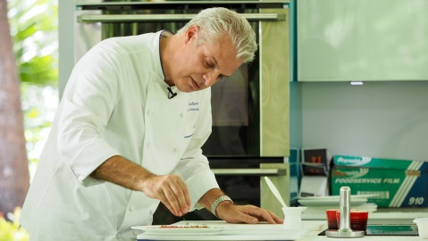 Eric Ripert seasoning food in a cooking demonstration