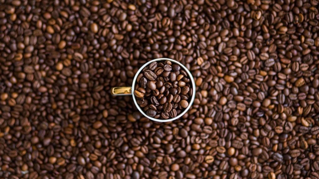 roasted coffee beans in a white mug