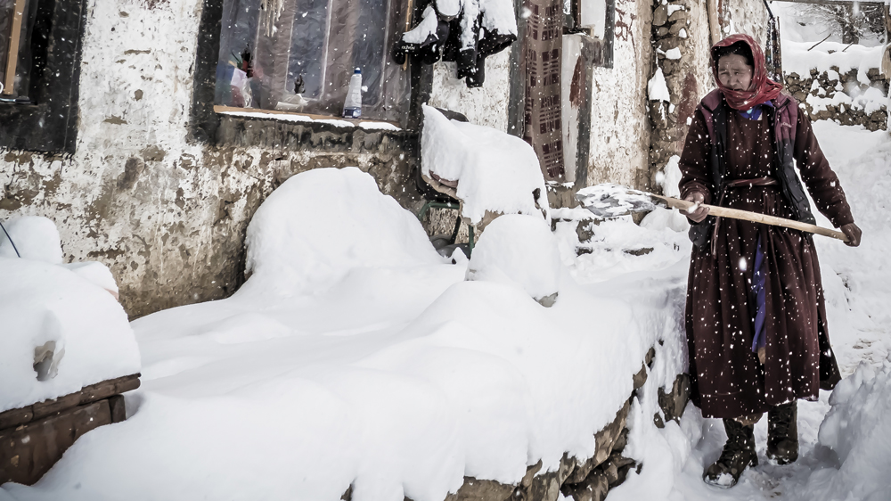 Woman shoveling in the snow-covered town of Indian Himalayas.