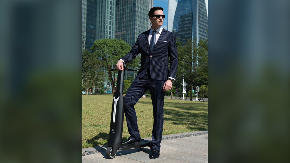Man in suit in park with Immotor Go electric scooter