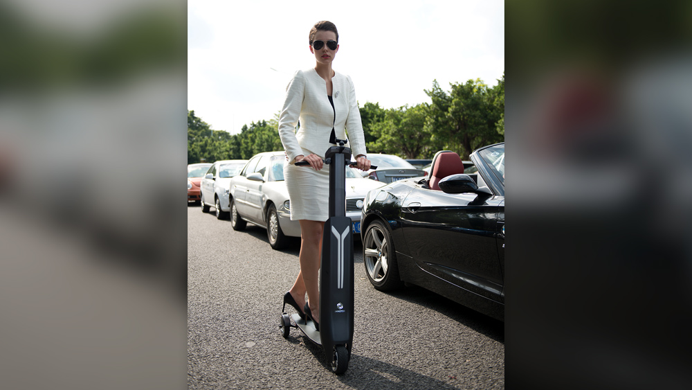 Woman in white riding Immotor Go scooter in parking lot
