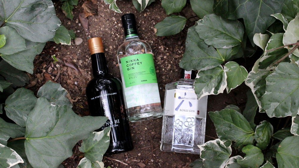 bottles of gin from Kyoto Distillery, Nikka, and Suntory among leaves