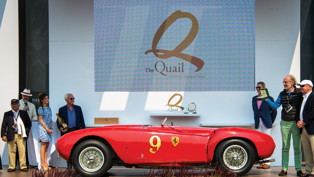 Pebble beach event with a ferrari on display