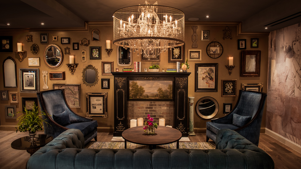 blue velvet couches with art-filled walls