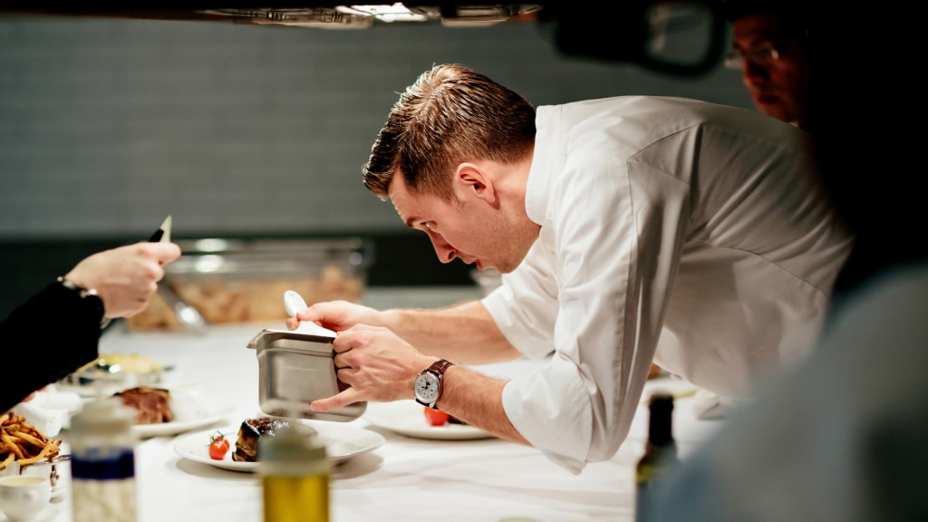 chef in white jacket plating dish in kitchen