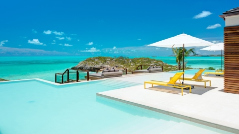 patio, infinity-edge swimming pool and waterfront view in Providenciales, Turks and Caicos