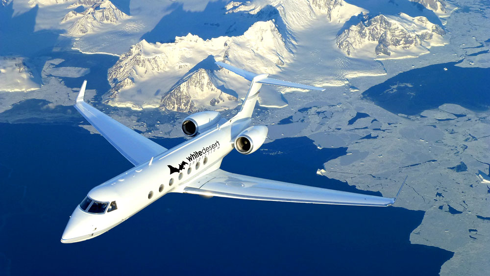 gulfstream private jet flying over mountains