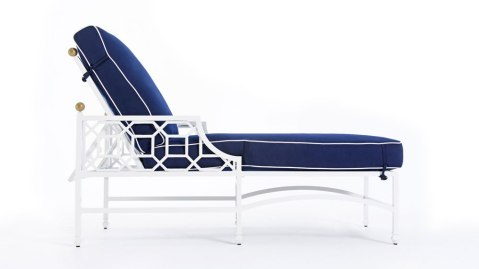 An outdoor chaise lounge designed by Barclay Butera for Castelle featuring classic fretwork in white and contrasted by chic navy cushions.