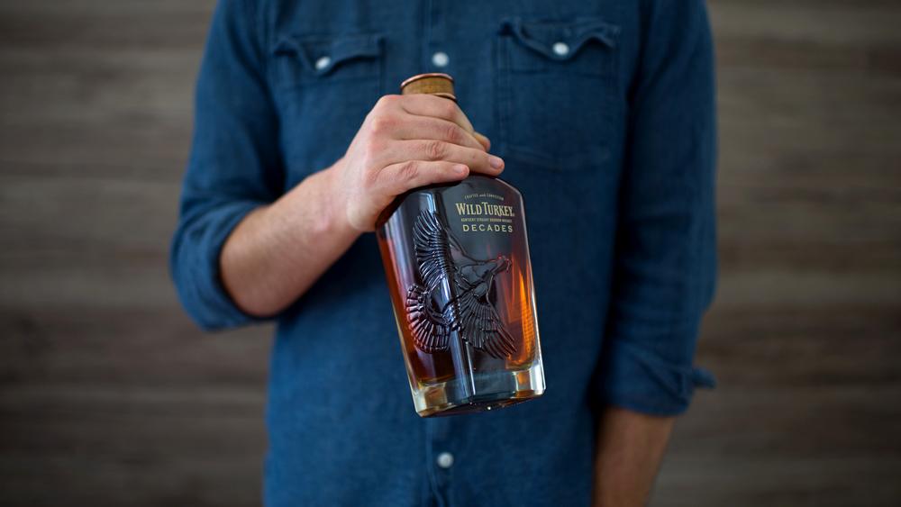 man holding Wild Turkey Decades bottle