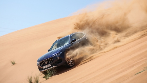 The Maserati Levante lets loose a spray of sand while descending a desert dune.