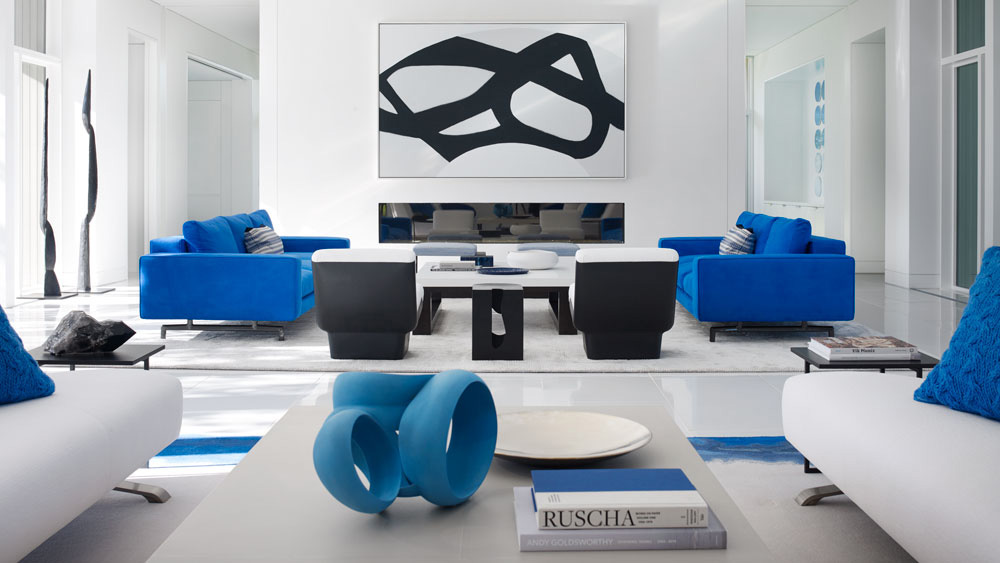 A modern living room with blue furniture and graphic artwork.