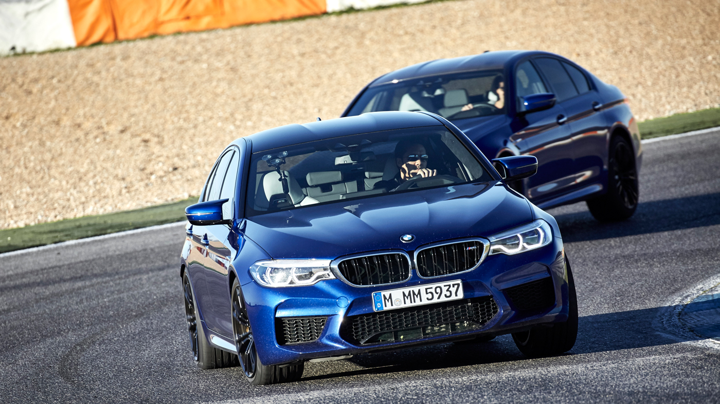 Two 2018 BMW M5s on a racetrack.
