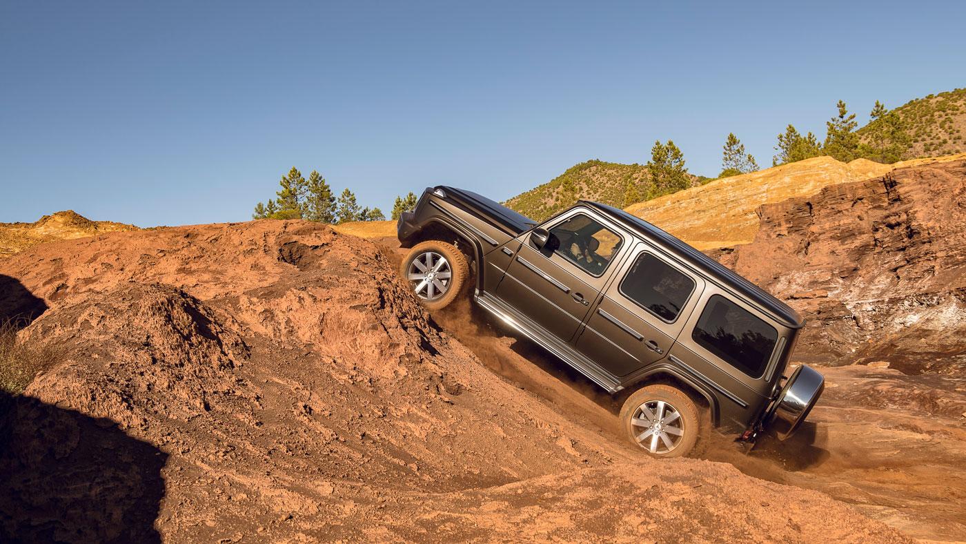 The 2019 Mercedes-Benz G550 climbing a dirt hill.
