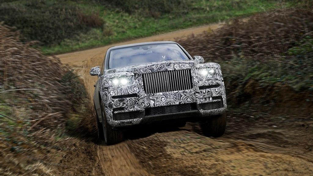 A Rolls-Royce Cullinan drives up a dirt road.