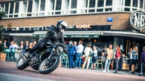 Husqvarna's Svartpilen motorcycle being ridden in an urban environment.