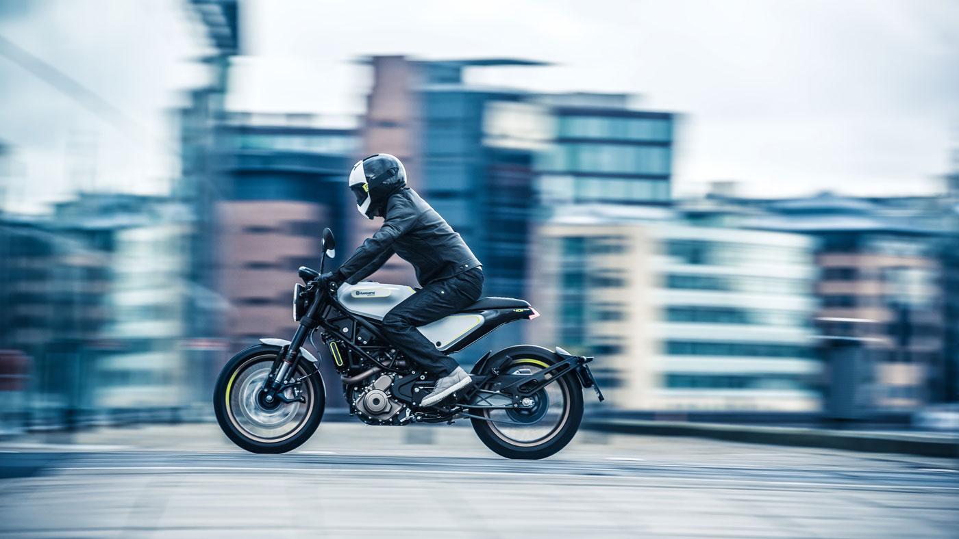 Husqvarna's Vitpilen motorcycle being ridden in an urban environment.