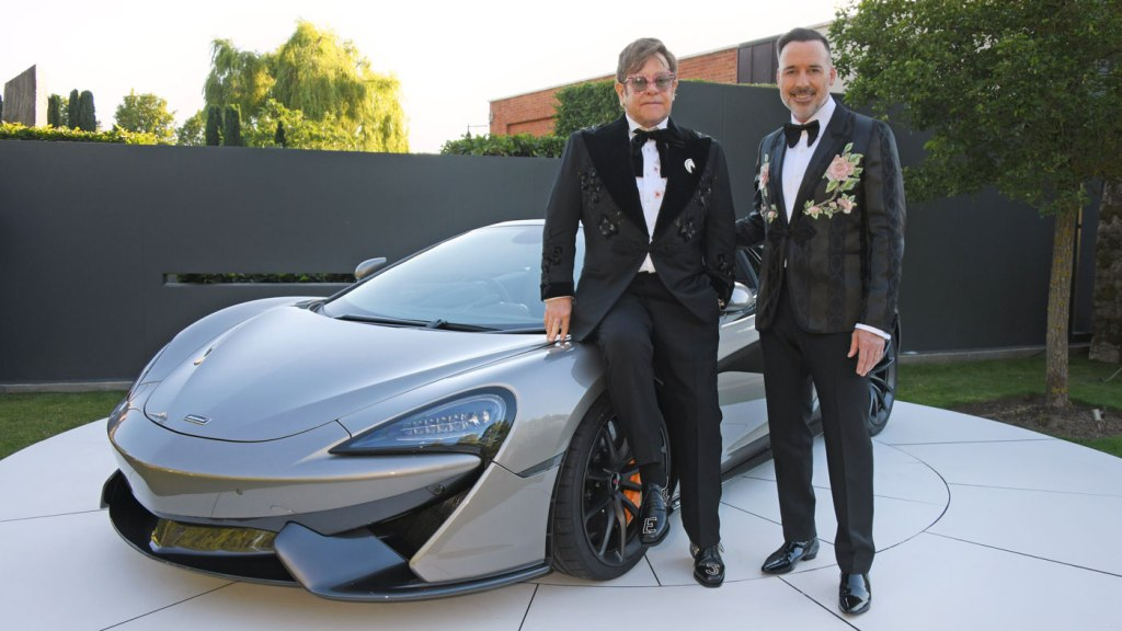 Elton John and David Furnish in front of the donated McLaren 570S Spider which was auctioned off for close to $1 million to benefit Elton John's AIDS Foundation