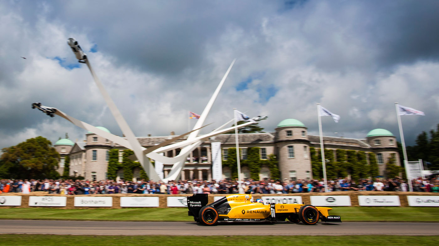 A racecar hurtles past Goodwood House. during the Goodwood Festival of Speed.