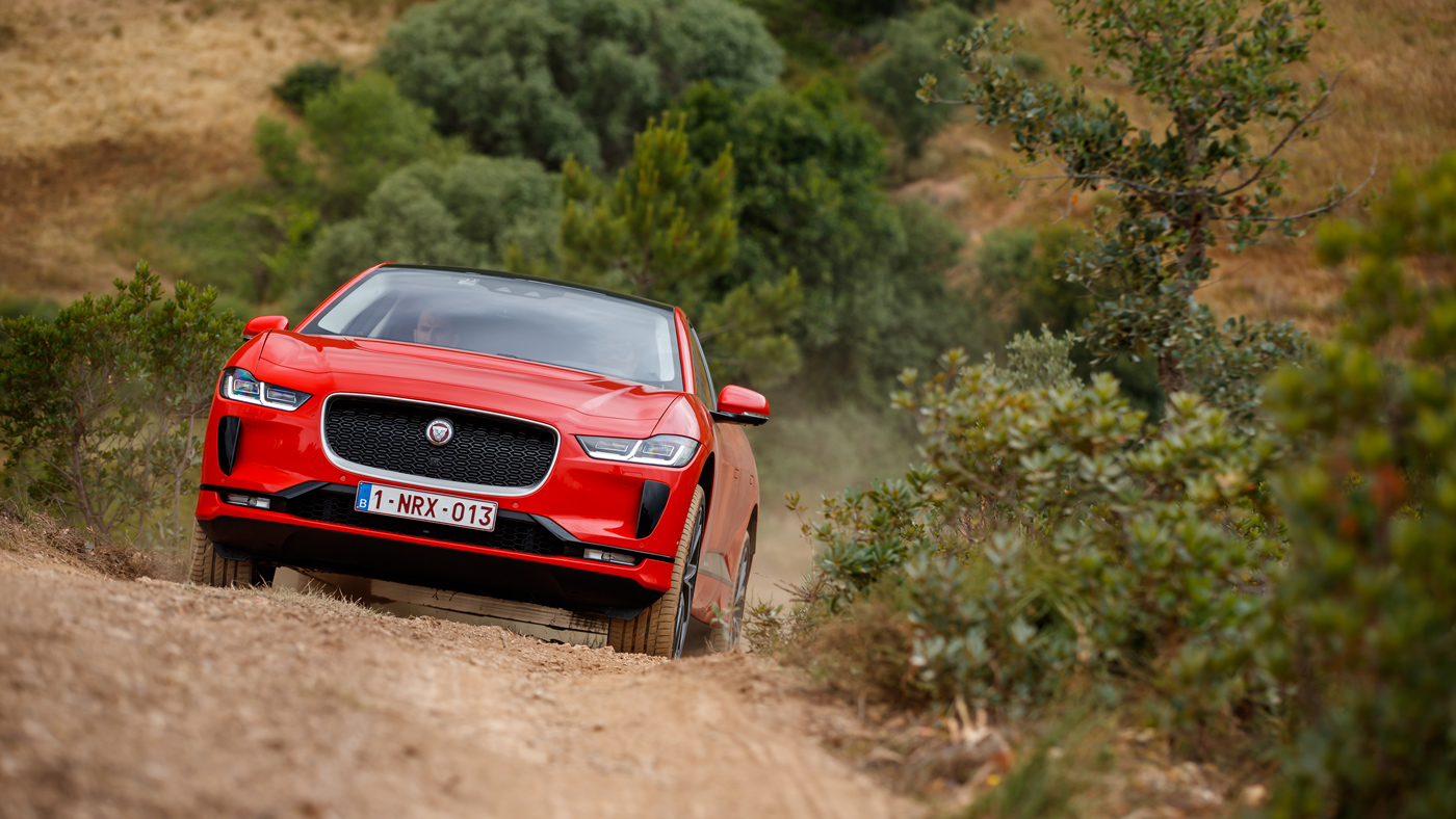 The 2019 Jaguar I-Pace climbing up a dirt track.