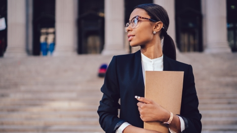 Pensive African American female lawyer in stylish formal suit holding folder with mock up area and looking away standing against courthouse. Half length of woman professional advocate with documents; Shutterstock ID 1008711700; Notes: Muse.com