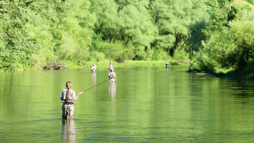 Fly fishing on the river in a rural place in the summer, young fishing woman standing in the water.Unrecognizable people in the background; Shutterstock ID 673626853; Notes: .