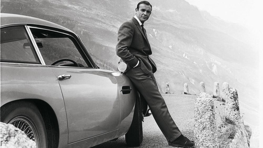 Actor Sean Connery, as James Bond, leans against a 1964 Aston Martin DB5.