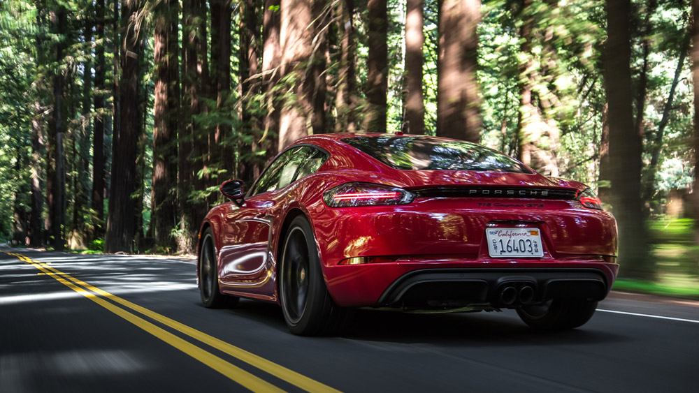 A Porsche 718 Cayman GTS driving on a wooded road.
