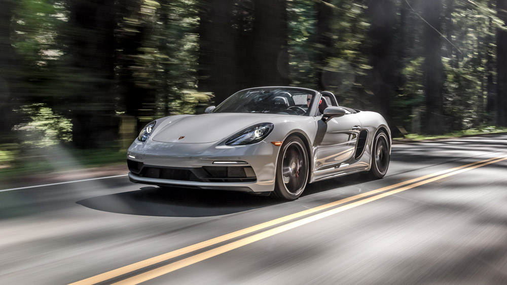 A Porsche 718 Boxter GTS driving on a wooded road.
